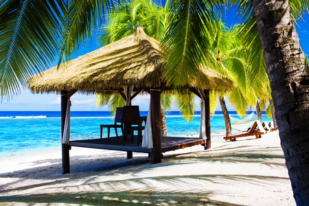 Tropical gazebo with chairs on deserted beach with palm trees