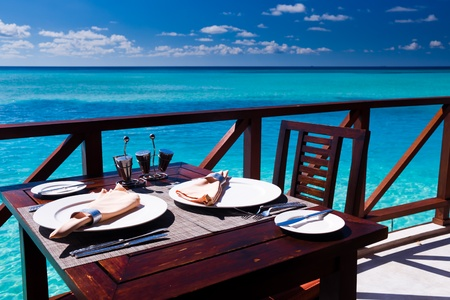indulging: Table setting at tropical beach restaurant in Maldives Editorial