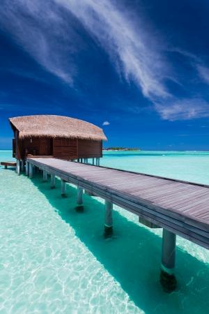 bora: Overwater bungalow in blue lagoon around tropical island