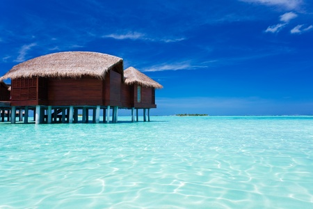 getaways: Overwater bungalow in blue lagoon around tropical island in Maldives