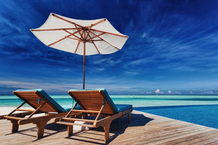 Deck chairs and infinity pool over amazing tropical lagoon Stock Photo - 11828416