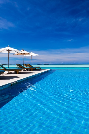 Deck chairs and infinity pool over amazing tropical lagoon Redactioneel