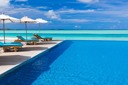 resorts: Deck chairs and infinity pool over amazing tropical lagoon Editorial