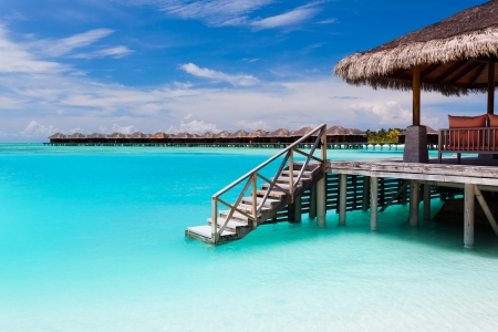 Over water bungalow with steps into amazing blue lagoon in Maldives Editorial