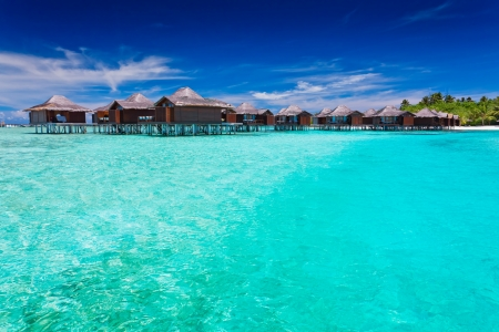 moorea: Overwater bungallows in blue lagoon around tropical island