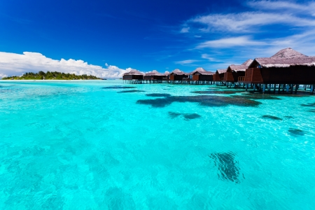 Overwater bungallows in blue lagoon around tropical island in Maldives