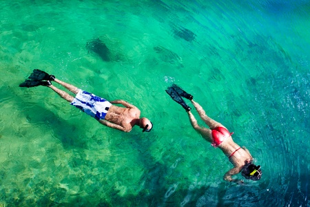 discover: Young couple snorkeling in clean water over coral reef Stock Photo