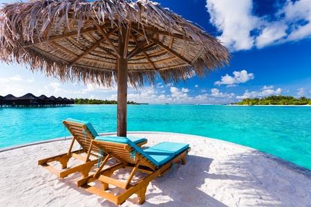2 つの椅子と見事な熱帯のビーチの傘