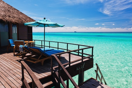 overlooking: Overwater villa balcony overlooking green tropical lagoon
