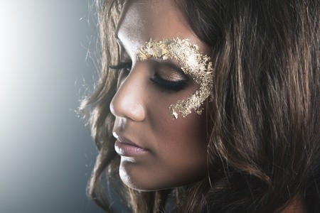 Studio fashion portrait with dark skin and golden makeup