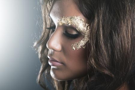 shimmer: Studio fashion portrait with dark skin and golden makeup