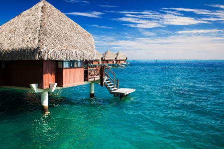 Over water bungalow with steps into green clear ocean