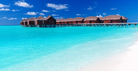 getaways: Overwater villas in blue tropical lagoon with white sandy beach Editorial