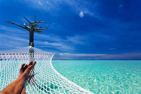 Mans crossed legs in hammock over tropical lagoon