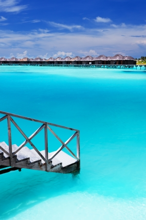 Steps into amazing blue lagoon with over-water bungalows Editorial