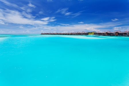 Overwater villas in tropical blue laggon of Maldives