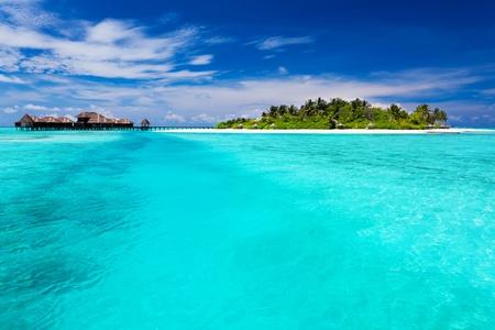 turquesa: Isla tropical con palmeras y bungalows sobre el agua