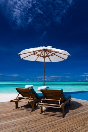 Deck chairs and infinity pool over blue tropical lagoon Standard-Bild