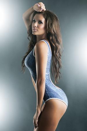 traje de bano: Perfil de una hermosa mujer en bikini azul de una pieza Foto de archivo