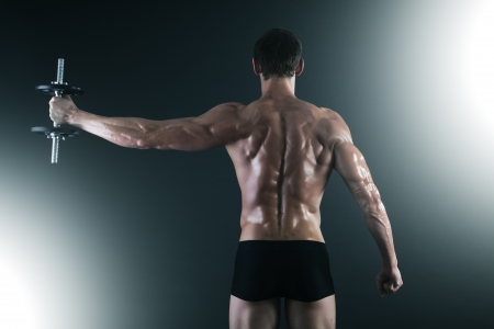 Back of young male bodybuilder doing weight exercise with dumbbells Standard-Bild