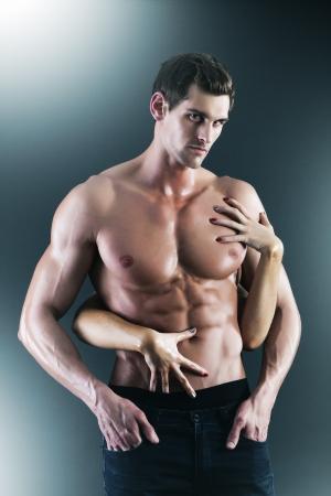 homme nu: Sexy homme muscl� nu et les mains des femmes se tenant la poitrine