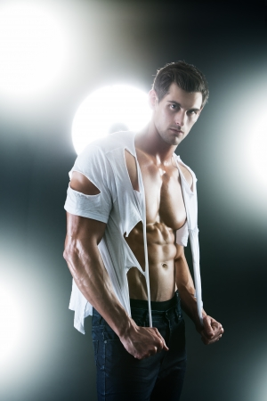 Sexy muscular male in white ripped shirt in studio photo