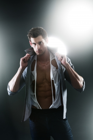 muscle shirt: Sexy muscular male in white ripped shirt in studio