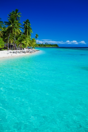 Tropical island in Fiji with sandy beach and pristine water photo