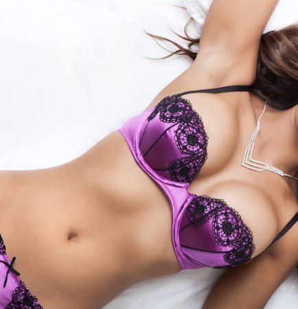 Beautiful sexy woman laying on her back in purple lingerie photo