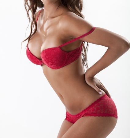 seni: Brunette sexy con grandi seni in lingerie rossa, vista laterale