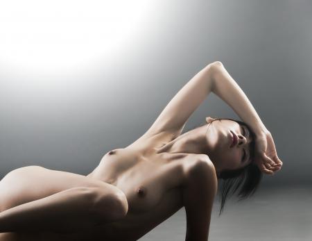 erotico: Giovane bella donna sexy con gli occhi chiusi sdraiata in studio