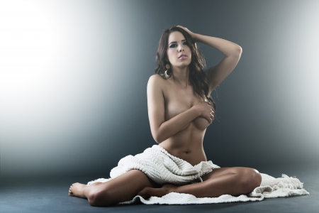 Beautiful Sensual nude woman sits covered by white cloth and hands photo