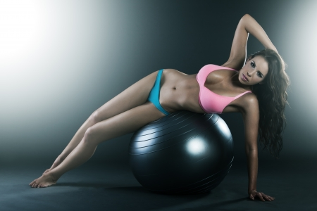 Pretty young woman laying on fit ball, doing workout, smiling