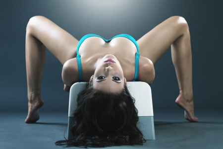 sexy breast: Young gorgeous woman gymnast excercising on bench Stock Photo
