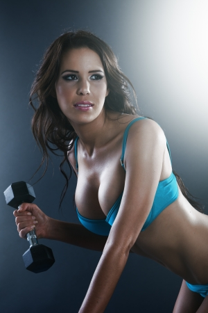 Athletic sexy young lady doing workout with weights photo