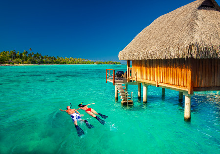 bungalows: Young couple snorkling from hut over blue tropical lagoon Stock Photo