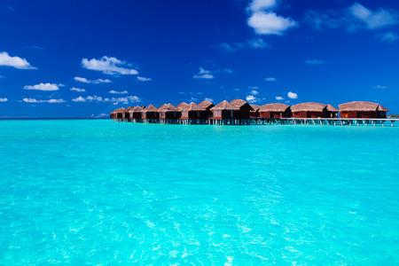 Villas sur pilotis dans le lagon tropical bleu de l'eau peu profonde Éditoriale
