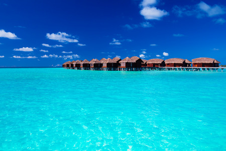 Overwater villas in blue tropical lagoon of shallow water