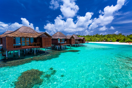 Over water bungalows with steps into amazing green lagoon with coral