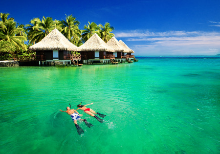 Couple snorkling in tropical lagoon with over water bungalows