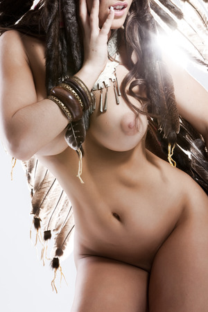 Nude standing woman dressed in traditional feather costume Stock Photo