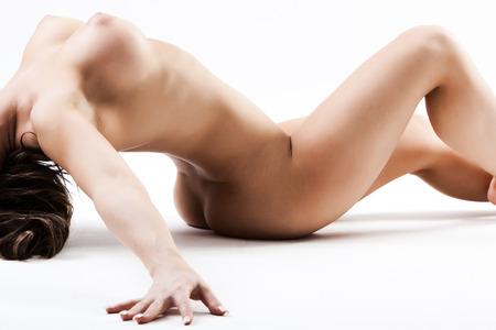 Joven mujer desnuda con pechos grandes haciendo lo imposible