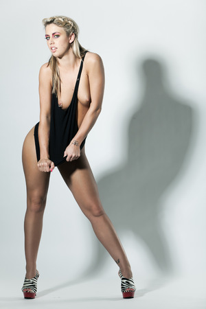 Slim topless young woman pulling the black dress photo