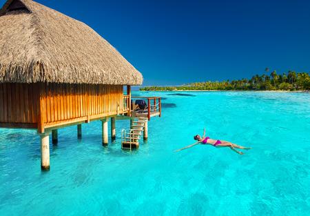 Woman swimming in tropical lagoon next to overwater villa Foto de archivo