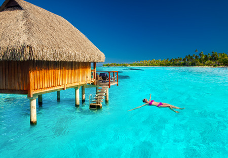 bungalows: Woman swimming in tropical lagoon next to overwater villa Stock Photo