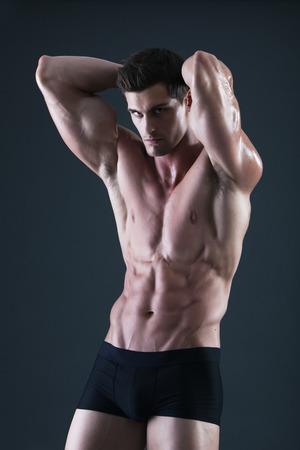 männer nackt: Junge mit nacktem Oberkörper muskulöser Mann in schwarzer Unterwäsche mit den Händen hinter dem Kopf Lizenzfreie Bilder