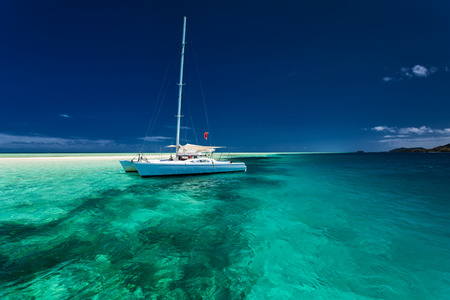 White catamaran in shallow tropical water with green snorkeling reef