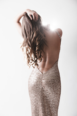 woman nude standing: Beautiful woman in elegant expensive evening shiny dress with naked rear