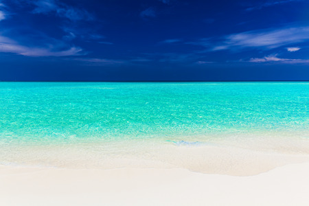 unspoilt: A vibrant shot of clear empty beautiful tropical beach with blue sky