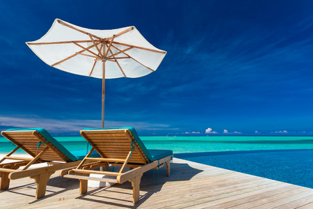 Deck chairs with umbrella overlooking infinity pool and tropical lagoon Imagens - 40154684